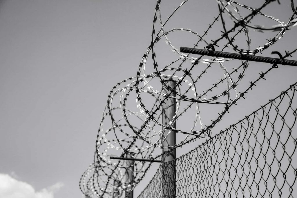 razor wire and barbed wire on the chain link fence