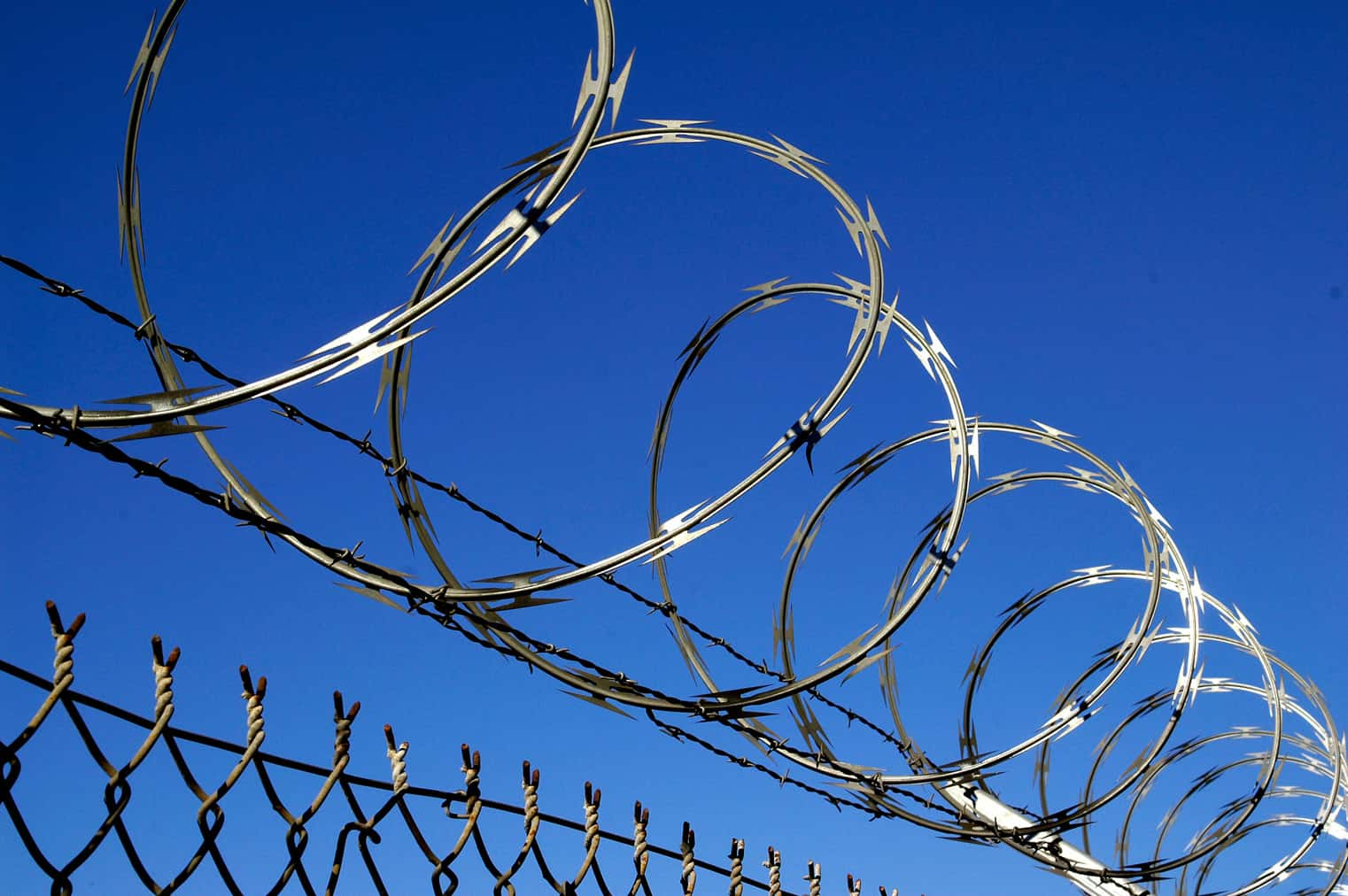 single spiral razor wire and barbed wire at the top of chain link fence