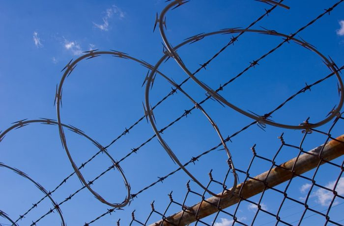 Spiral razor wire and barbed wire at the top of chain link fence