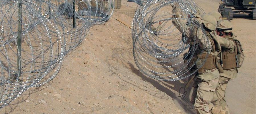 Soldiers are deploying razor wire barriers