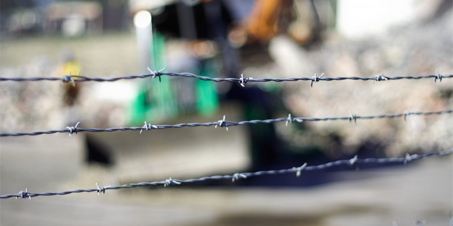 barbed wire on top of the chain link fence